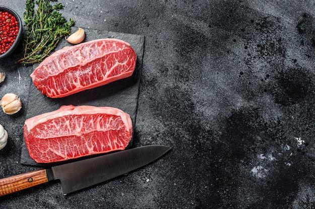 Bistecca con lama superiore di ostriche twagyu di carne biologica cruda. sfondo nero. vista dall'alto. copia spazio.