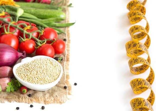 Quinoa organica cruda e verdure crude isolate sulla fine di bianco su