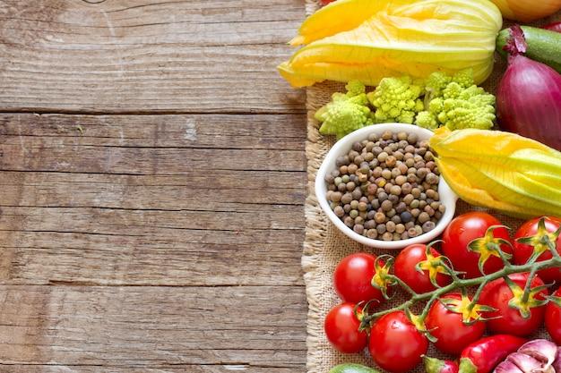 Fagioli di roveja organici crudi in una ciotola con le verdure crude su una fine di legno della tavola su con lo spazio della copia
