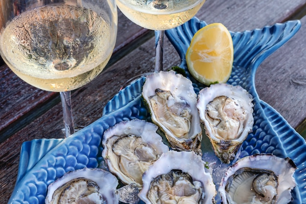 Piatto di ostriche crude con limone con bicchieri di champagne