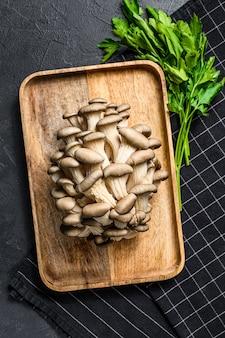 Funghi di ostrica crudi in una ciotola di legno con prezzemolo. cibo organico. sfondo nero. vista dall'alto