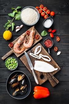 Ingredienti per paella cruda su superficie di legno nera, vista dall'alto
