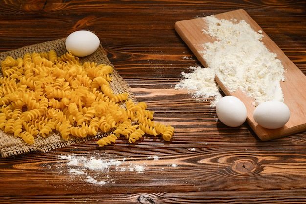Pasta cruda e ingredienti per pasta su fondo di legno.