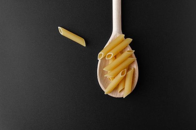 Penne rigate crudo della pasta sul cucchiaio di legno sulla tavola nera.