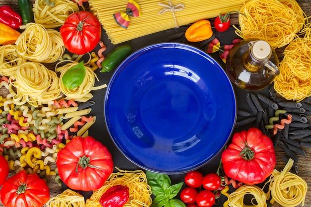 Pasta cruda con ingridients e copia spazio sul piatto blu
