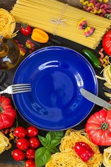Pasta cruda con ingridients e copia spazio sul piatto blu vuoto