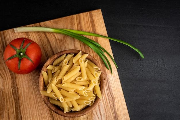 Pasta cruda in ciotola di legno con formaggio, pomodoro e cipolla verde su sfondo nero.