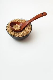 Orzo perlato crudo in un cucchiaio di legno e in un piatto