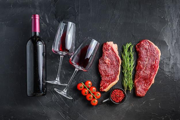 Bistecche di picanha crude con condimenti ed erbe aromatiche vicino a bottiglia e bicchiere di vino rosso, su vista da tavolo con texture nera