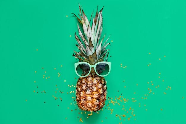 Ananas crudo con glitter dorati. concetto tropicale laico piatto