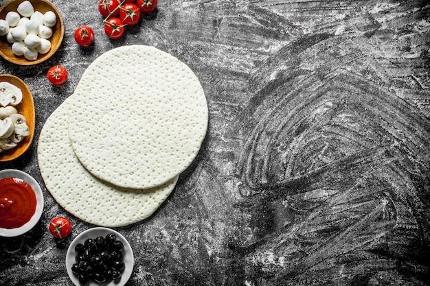 Pizza cruda. l'impasto con gli ingredienti per fare la pizza. su fondo rustico