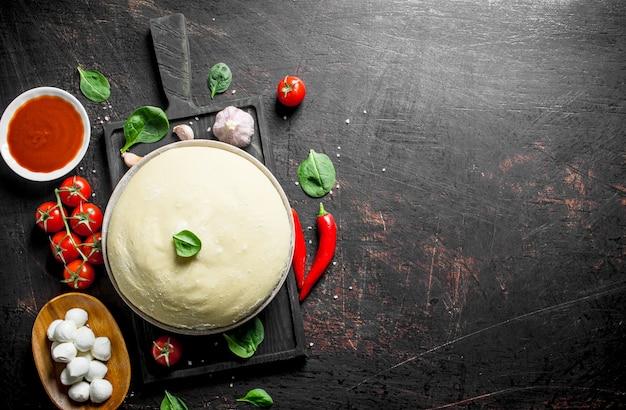 Pizza cruda. impasto con vari ingredienti per cucinare la pizza fatta in casa. su fondo rustico scuro