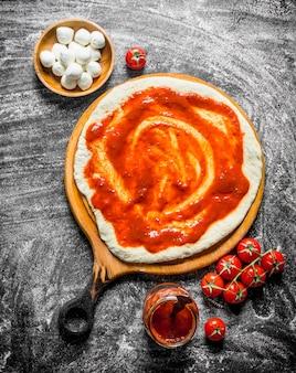 Pizza cruda. pasta stesa con concentrato di pomodoro, mozzarella e pomodorini freschi. su fondo rustico
