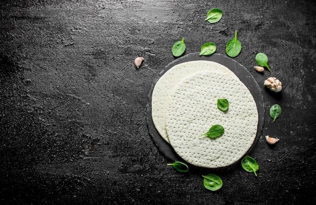 Pizza cruda. pasta rotonda stesa con spinaci e aglio. su sfondo nero rustico