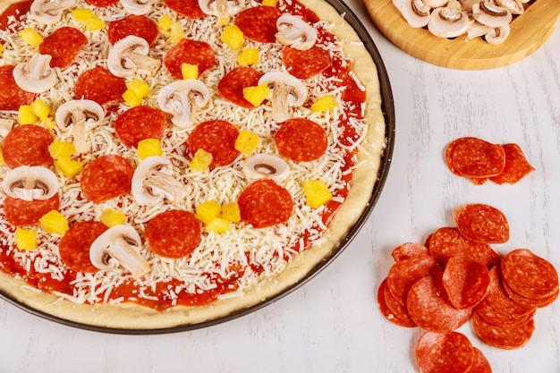 Pizza cruda con funghi, peperoni e ananas.