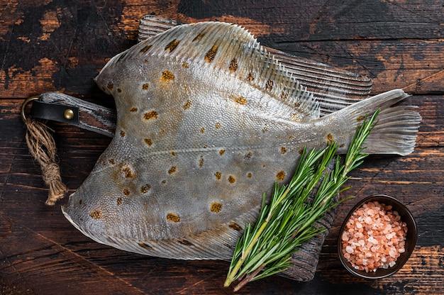 Pesce piatto crudo passera di mare sul bordo del macellaio con coltello. fondo in legno scuro. vista dall'alto.