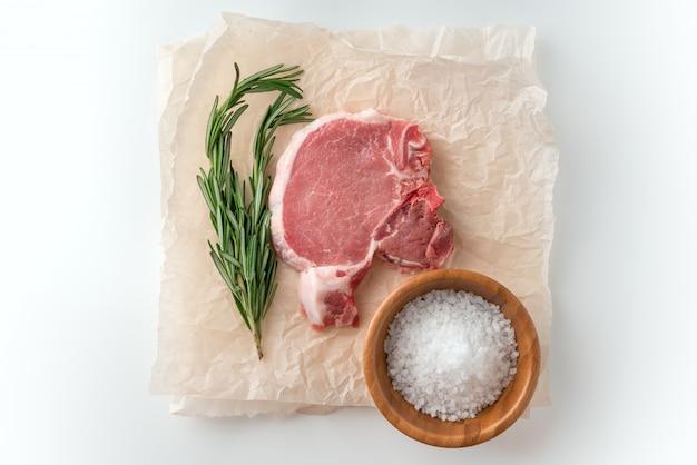 Cotoletta cruda del porco con le spezie per la griglia o cucinando sulla superficie bianca