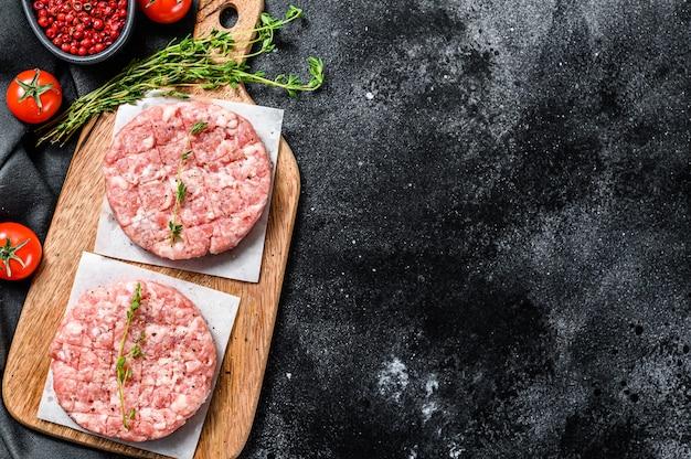 Cotolette di maiale crude, tortino di carne macinata su un tagliere. trito biologico. sfondo nero. vista dall'alto. copia spazio.