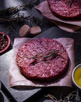 Cotoletta di hamburger di maiale crudo con spezie su sfondo scuro. produzione casalinga di semilavorati. cibo semplice.