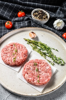 Tortino di maiale crudo, cotolette di carne macinata su un tagliere. trito biologico. sfondo grigio. vista dall'alto.
