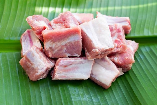 Costolette di maiale crude su sfondo di foglie di banana