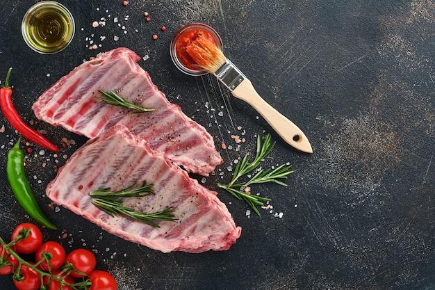 Costolette di maiale crude o carne cruda fresca con spezie su vassoio di legno nero con paprika, spicchi d'aglio ed erbe aromatiche. fondo strutturato scuro con lo spazio della copia per testo.