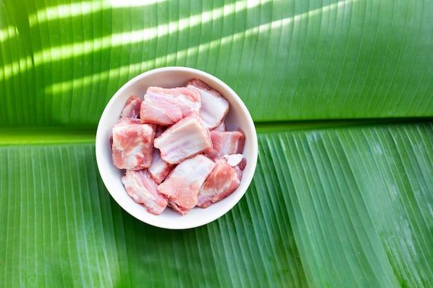 Costolette di maiale crude in ciotola bianca sfondo foglia onbanana.
