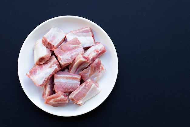 Costolette di maiale crude in piatto bianco su sfondo scuro.
