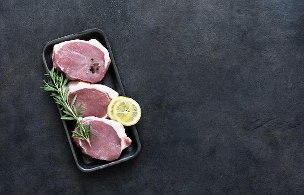 Bistecche di maiale crude in un vassoio nero con spezie e limone su uno sfondo di cemento, vista dall'alto.
