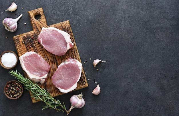 Bistecche di maiale crude su una tavola di legno con spezie, rosmarino e limone su uno sfondo di cemento nero.