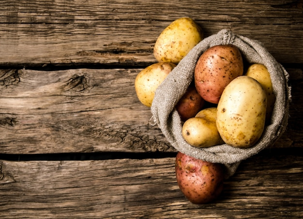 Cibo a base di patate crude. patate fresche in un vecchio sacco su fondo in legno. posto libero per il testo. vista dall'alto