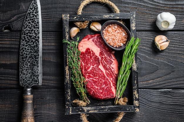 Bistecca di carne di manzo cruda costata di manzo in un vassoio di legno del macellaio con erbe