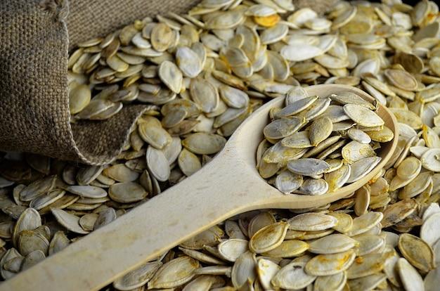 Semi di zucca crudi si chiudono in un cucchiaio di legno