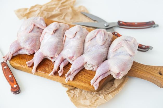 Le quaglie crude giacciono su una tavola di legno. preparato per il taglio di carne magra dietetica.