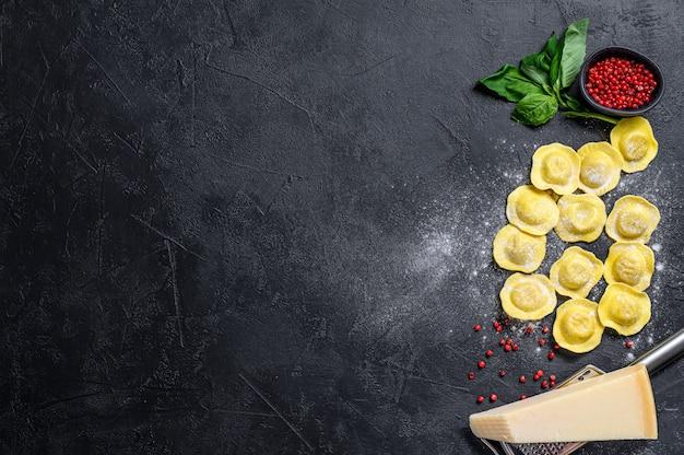 Ravioli crudi il processo di preparazione dei ravioli italiani fatti in casa. muro nero. vista dall'alto. spazio per il testo