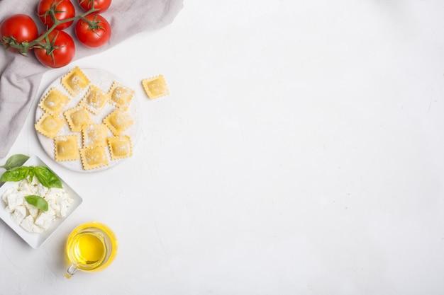 Ravioli crudi con basilico, formaggio e pomodori su fondo bianco, vista superiore