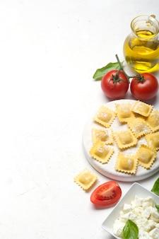 Ravioli crudi con basilico, formaggio e pomodori su fondo bianco