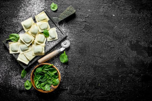 Ravioli crudi con spinaci sulla tavola rustica nera.