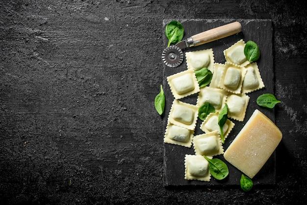 Ravioli crudi con spinaci e formaggio sulla tavola rustica