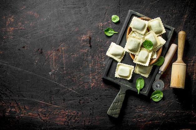 Ravioli crudi con carne di vitello su un tagliere sul tavolo rustico scuro.