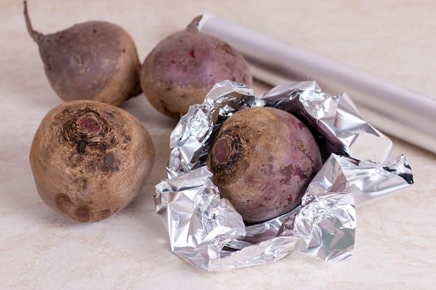 Barbabietola rossa cruda preparata per la cottura in forno. barbabietola rossa avvolta in un foglio di alluminio