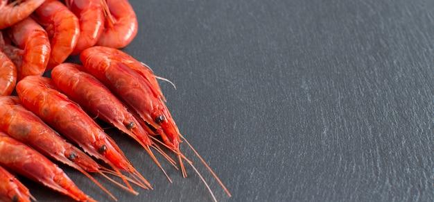 Gamberetti rossi crudi sopra la fine scura del fondo su con lo spazio della copia