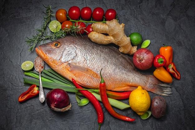 Red snapper pesce crudo con spezie ed erbe ingredienti per cucinare su sfondo scuro., vista dall'alto