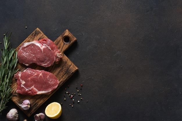 Bistecca di manzo cruda ribeye cucinata con ingredienti: sale, pepe, limone. vista dall'alto con copia spazio