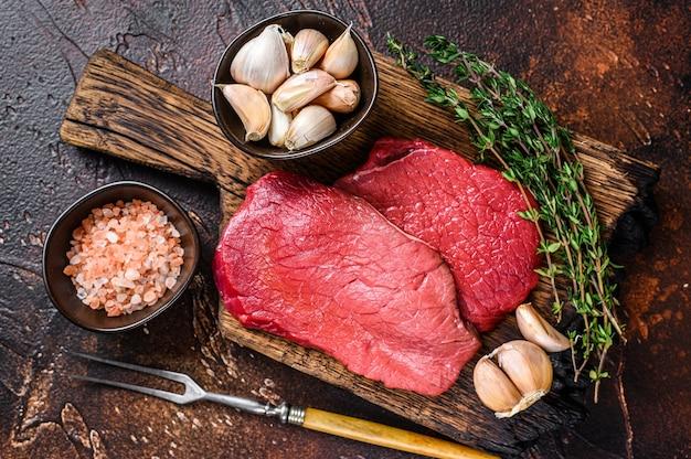 Bistecche di carne di manzo cruda sul tagliere di legno del macellaio