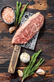 Bistecca cruda del cappuccio della fesa su una mannaia della carne. fondo in legno scuro. vista dall'alto.