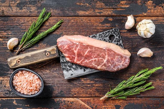 Bistecca cruda del cappuccio della fesa su una mannaia della carne