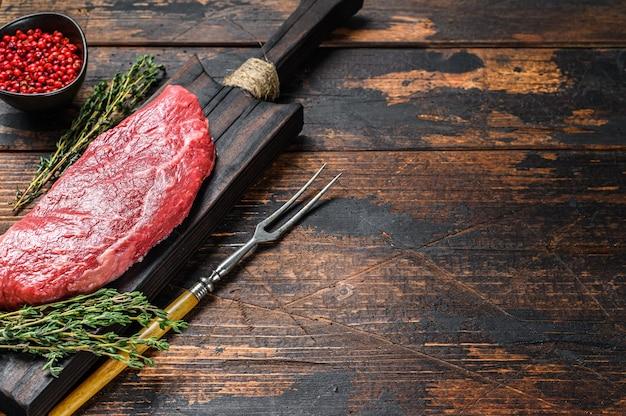 Bistecca di manzo cruda, carne di manzo. sfondo in legno scuro. vista dall'alto. copia spazio.