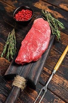 Bistecca di manzo cruda, carne di manzo. sfondo in legno scuro. vista dall'alto.