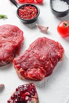 Bistecca cruda, carne di manzo di fattoria con condimenti, rosmarino, aglio, granato. sfondo bianco con texture. vista laterale.